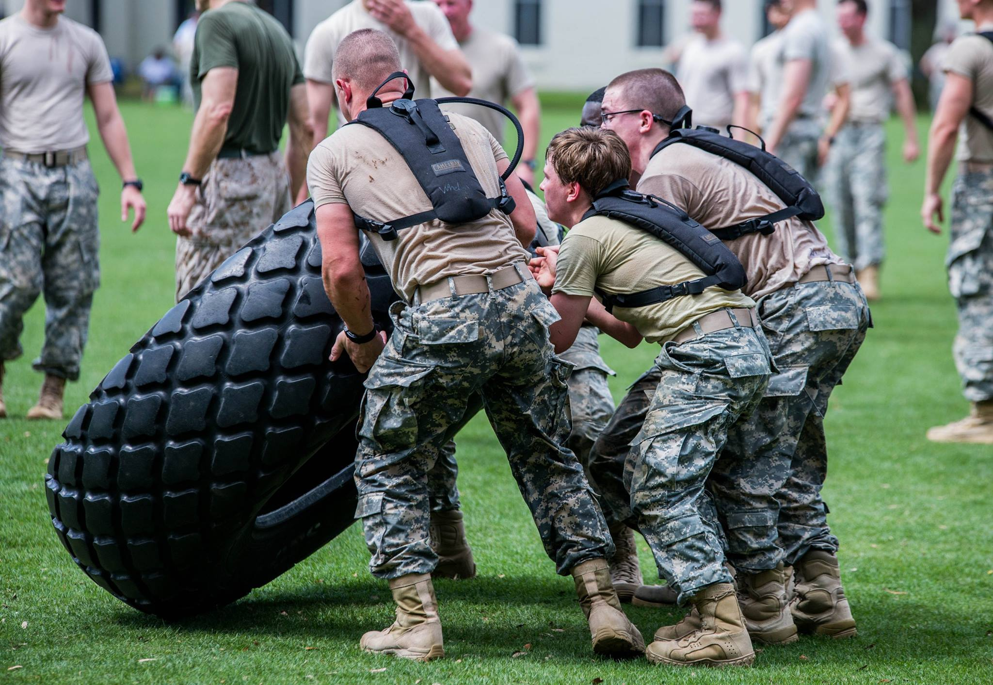 "Cadets work together to flip a tire during the ""Gauntlet."" photo by Stacy Carter Photography Studios"